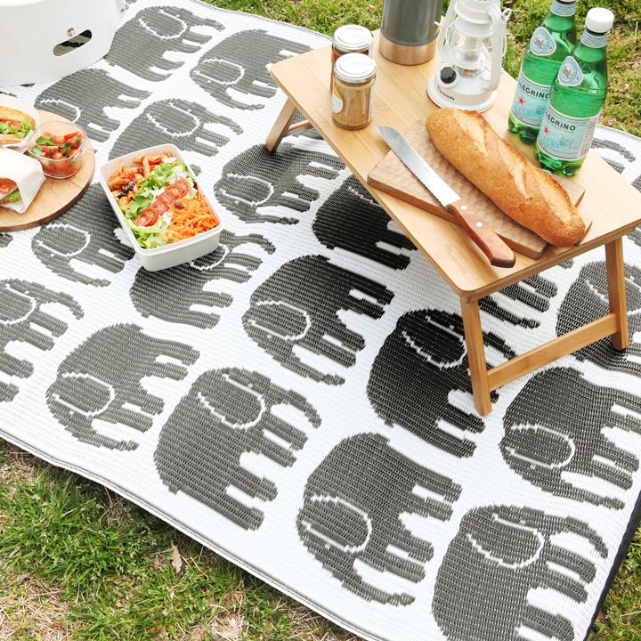 芝生に敷いた像柄のストローラグ。上にはお弁当や飲み物、テーブルなど。