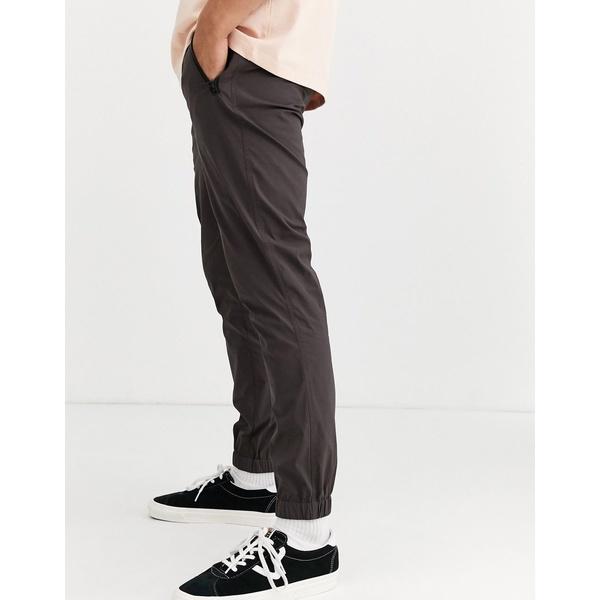 エイソス メンズ カジュアルパンツ ボトムス ASOS DESIGN tapered woven sweatpants in nylon with webbed belt in brown Brown