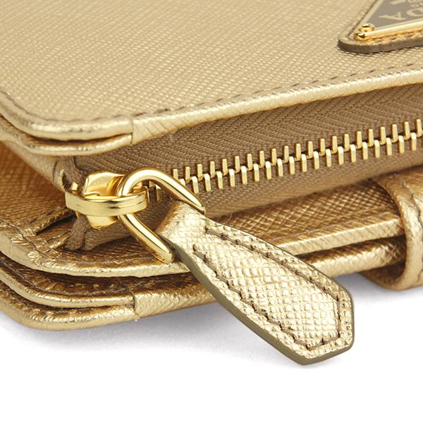 d79e436f44c6 ゴージャスなゴールドカラーのサフィアーノレザーとプラダを象徴するトライアングルロゴが目を惹く二つ折り財布。カードやレシートなどが収まるポケットが機能的に配置  ...