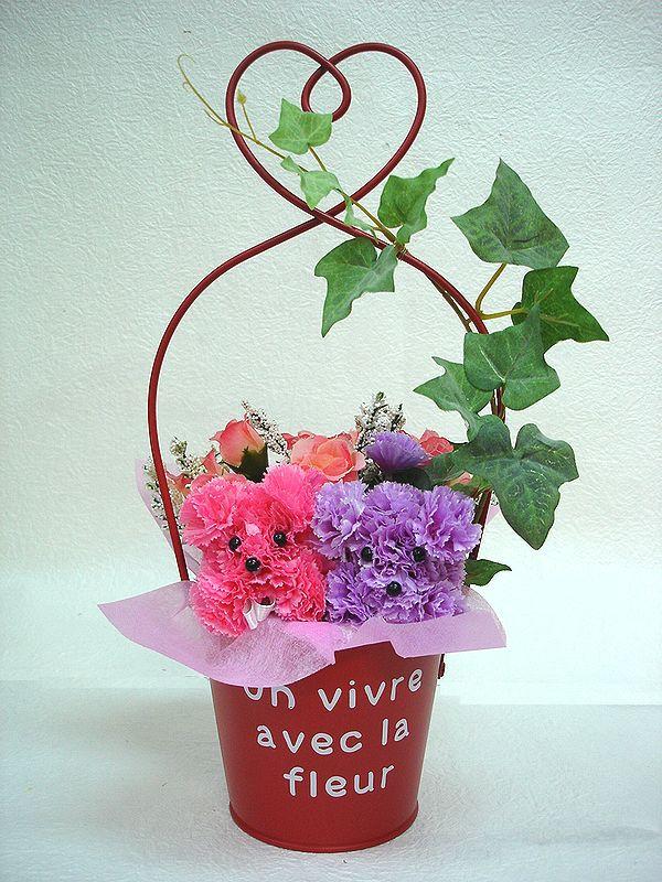 赤いブリキバケツで 2匹のプードルが入った造花アレンジ ピンク パープル2匹のプードルがかわいらしく見つめています ブリキポットプードル 花 フラワーギフト 結婚祝い 正規取扱店 誕生日 歓迎 アレンジメント 記念日 期間限定で特別価格 送迎 お祝い 造花 退職祝い 還暦