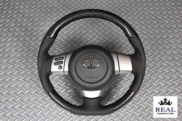 【 FJクルーザー GSJ15W (北米&国内仕様装着可)用 】 レアル ステアリング オリジナルシリーズ (プラチナブラックカーボン / IKURA モデル) 品番: FJ-PX-BKC (REAL Steering 純正交換タイプ) ※送料無料 (沖縄県および離島は除く)