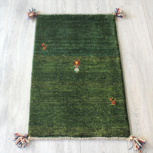 カシュカイ族の手織りギャッベ・ウール100%ミニギャッベ63x41cm グリーン・スカートをはいた女の子
