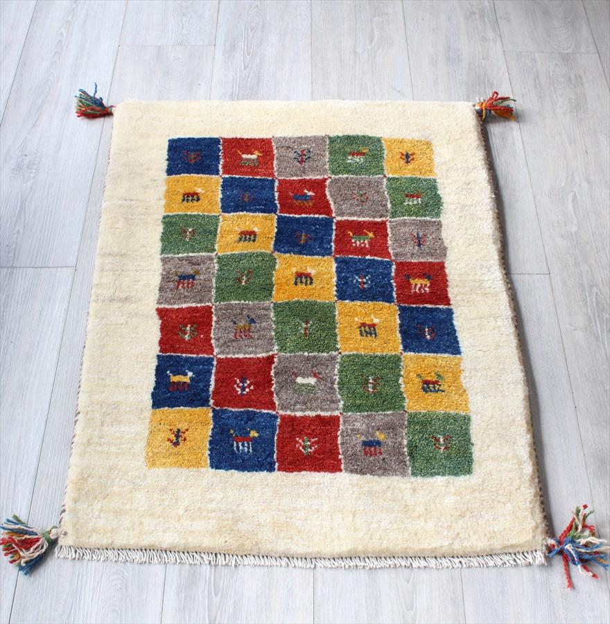 ギャッベ イラン直輸入 手織りラグ・玄関マットサイズ89x63cm アイボリー カラフルなタイル 動物と植物のモチーフ