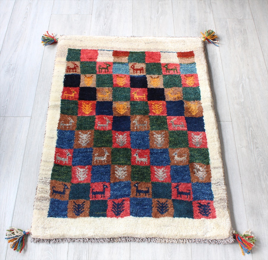 ラグ・ギャッベ(ギャベ)カシュカイ族の手織りラグ・玄関マットサイズ87x61cm アイボリー カラフルなタイル 動物と植物のモチーフ