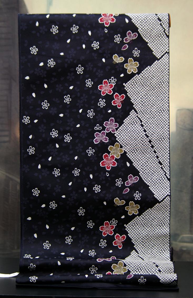 正絹名古屋帯【丸巻反物】シルク100%【お茶会・お洒落着物用】ブラック地色に桜吹雪の柄。名古屋帯は袋帯よりも簡単に締められるとても重宝な帯といえます。7000円追加で帯芯付き本仕立てもいたします。京都、日本製