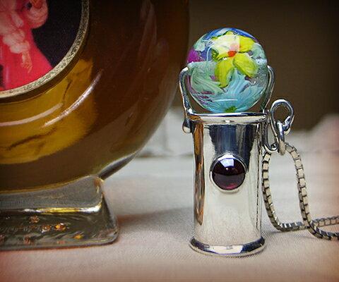 K & D カレイドスコープ ペンダント  ガーネットベネチアングラス ユニセックスペンダント 万華鏡 中央の宝石は5mm×5mmの存在感のあるガーネット。彫りの装飾はなくシンプルなフォルム。ベネチアンガラスは青、緑、紫の3色をご用意致しました。