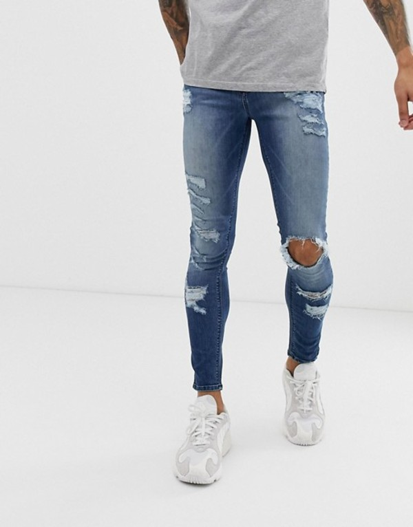 エイソス メンズ デニムパンツ ボトムス ASOS DESIGN spray on jeans in power stretch with heavy rips in mid wash blue Mid wash blue
