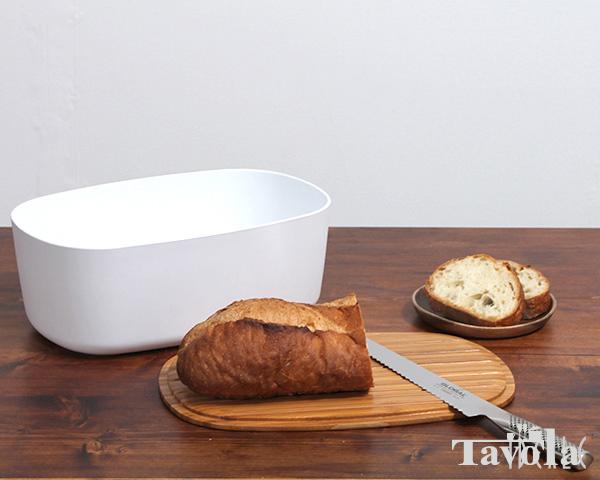 白いブレッドケースと木のボードの上のフランスパン